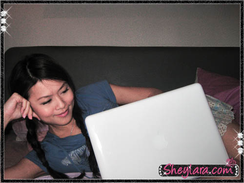Sheylara pretending to use a Macbook